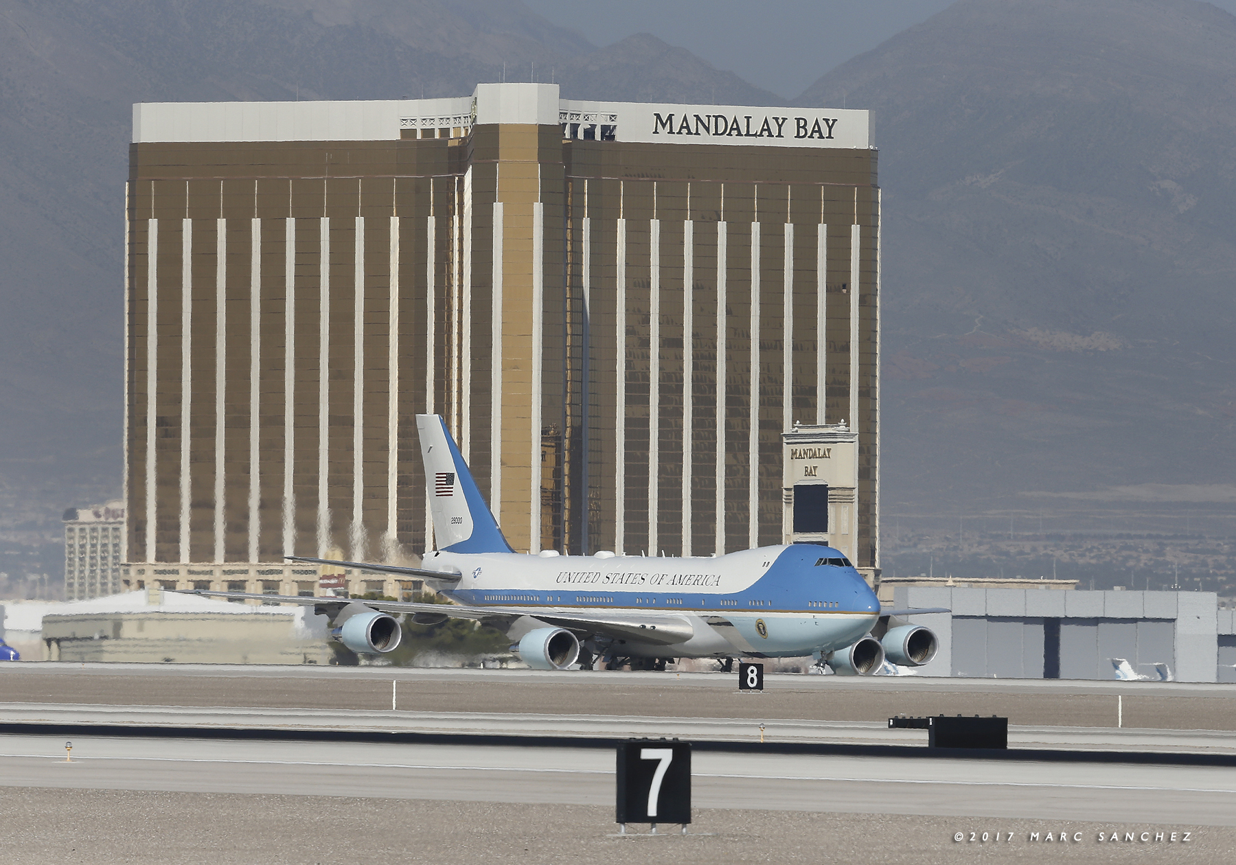 Image of Air Force One with US President Donald Trump and First Lady Melania Trump arrive at McCarran International Airport in Las Vegas on October 4, 2017, with the broken window of the 32nd floor of the Mandalay Bay resort in the background. President Donald Trump arrived in Las Vegas, where he will meet survivors of the most deadly mass shooting in modern US history.